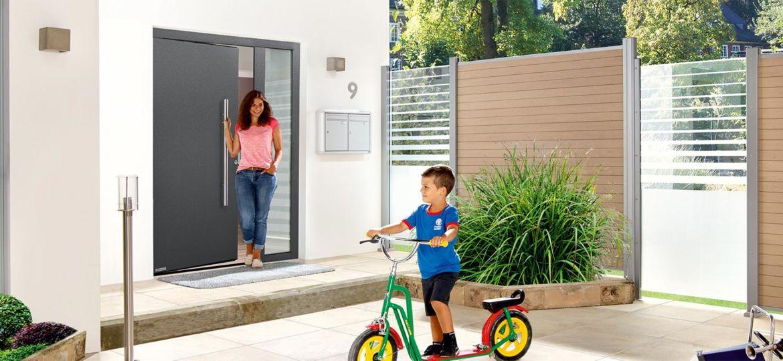 Mutter und Kind auf Roller stehen vor dem Haus